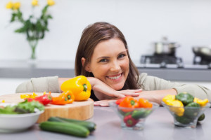 cheerful-woman-leaning-on-the-counter-of-her-kitchen-large